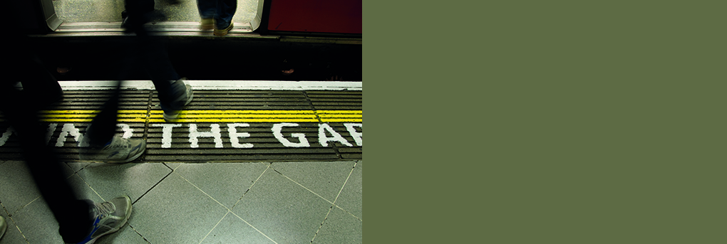 Passengers stepping from platform through train doors, mind the gap text on platform.