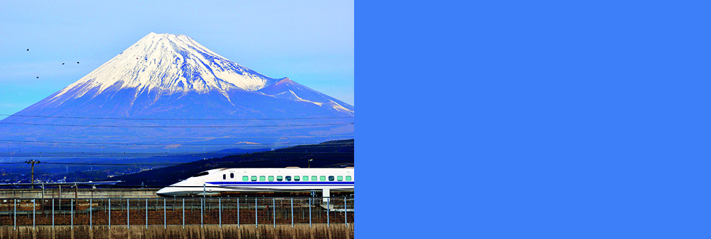 Bullet train passing through Japanes countryside with Mount Fuji in background.