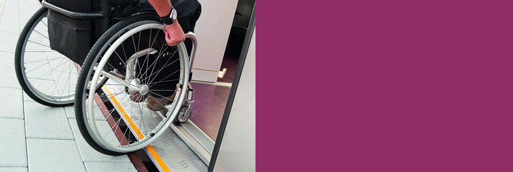 Wheelchair user negotiating door system onto train.